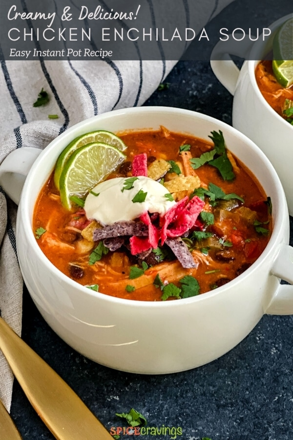enchilada soup in white soup crock topped with sour cream, cilantro and tortilla strips