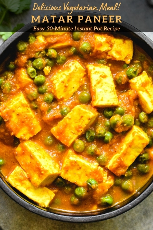 close-up of paneer and pea curry in black bowl