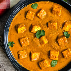 Paneer tikka masala curry in blue bowl garnished with cilantro