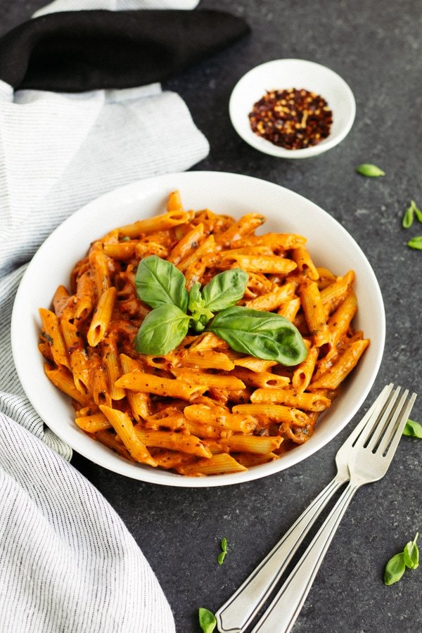 creamy penne vodka recipe in white bowl garnished with fresh basil with two forks and red pepper flakes on the side