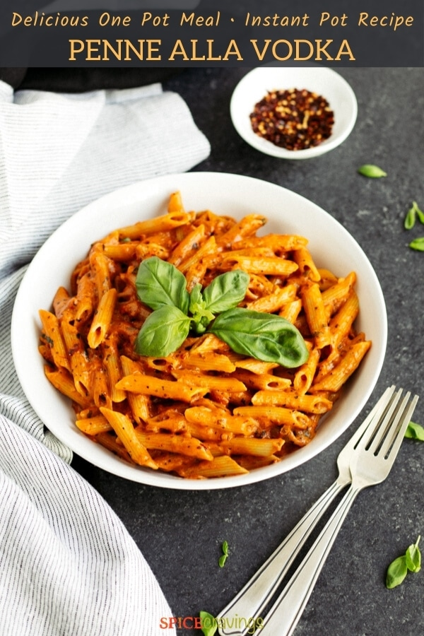 penne vodka recipe in white bowl garnished with fresh basil with two forks on the side