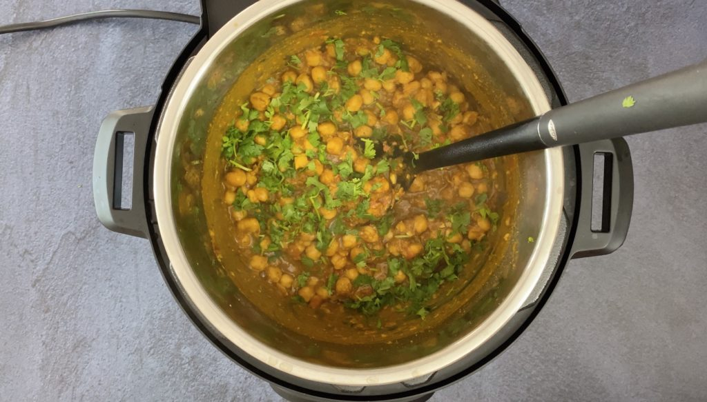 chana masala filling with fresh cilantro and black spoon in instant pot