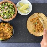 hand spooning chana masala mix on corn tortilla with spiced chickpeas, cucumber salsa and lime wedges in bowls