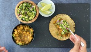 hand spooning cucumber salsa on corn tortilla with spiced chickpeas, cucumber salsa and lime wedges in bowls