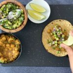 handsqueezing lime over indian chickpea taco with spiced chickpeas, cucumber salsa and lime wedges in bowls