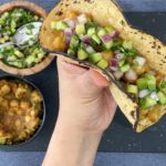 hand holding chana masala taco with cucumber salsa and spiced chickpeas in bowls