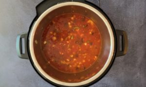 water, tomatoes, corn, black beans and aromatics in instant pot