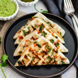 four Indian-style waffle halves on a plate, made with cilantro and tomato