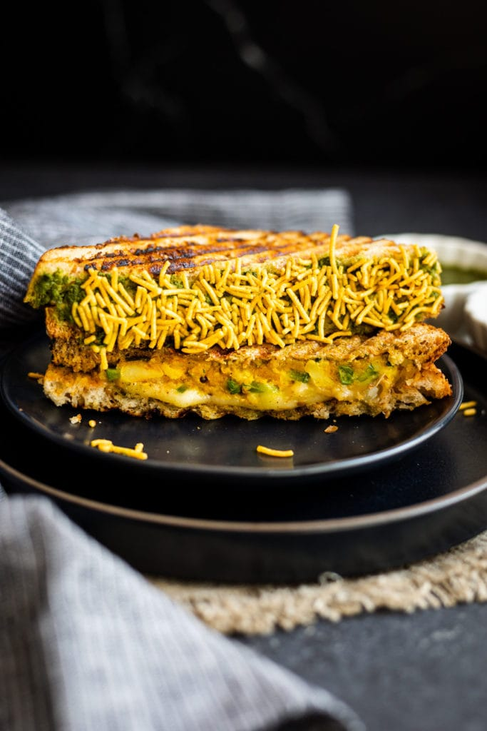 bombay cheese toastie coated in namkeen on black plate