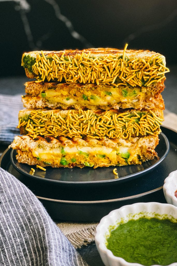 stack of bombay cheese toastie coated in namkeen on black plate