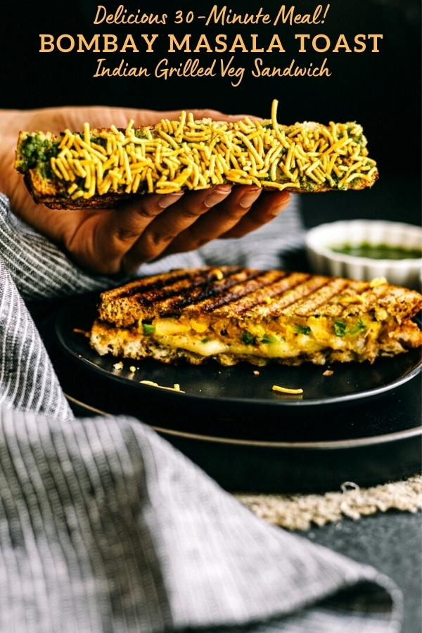 hand holding half of bombay masala toast recipe coated in namkeen