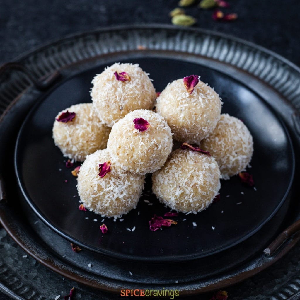 Plate of stacked coconut ladoo, topped with dried rose leaf
