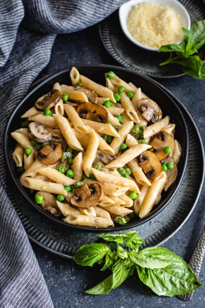 creamy mushroom pasta recipe in black bowl with grated cheese and fresh basil