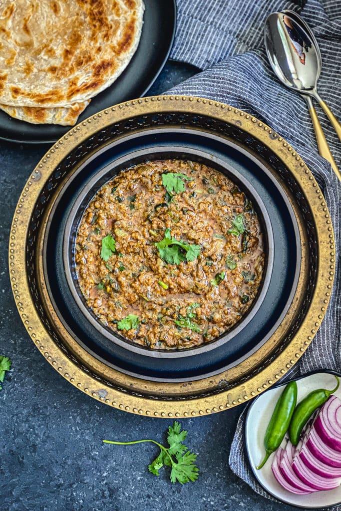 pumjabi keema recipe in black bowl garnished with cilantro sprigs