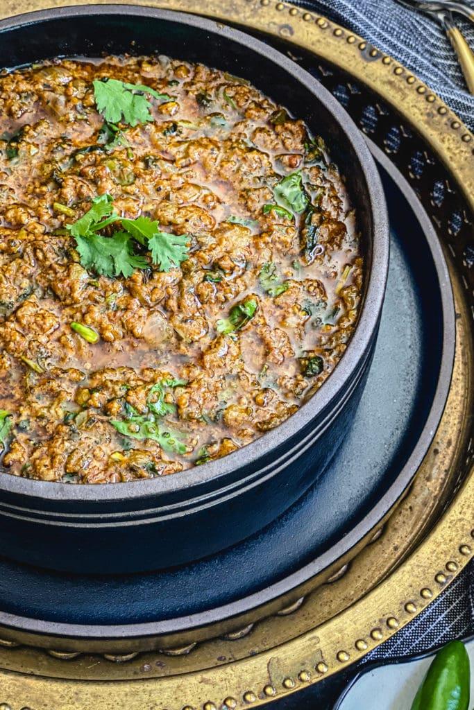 keema recipe in black bowl garnished with cilantro sprigs