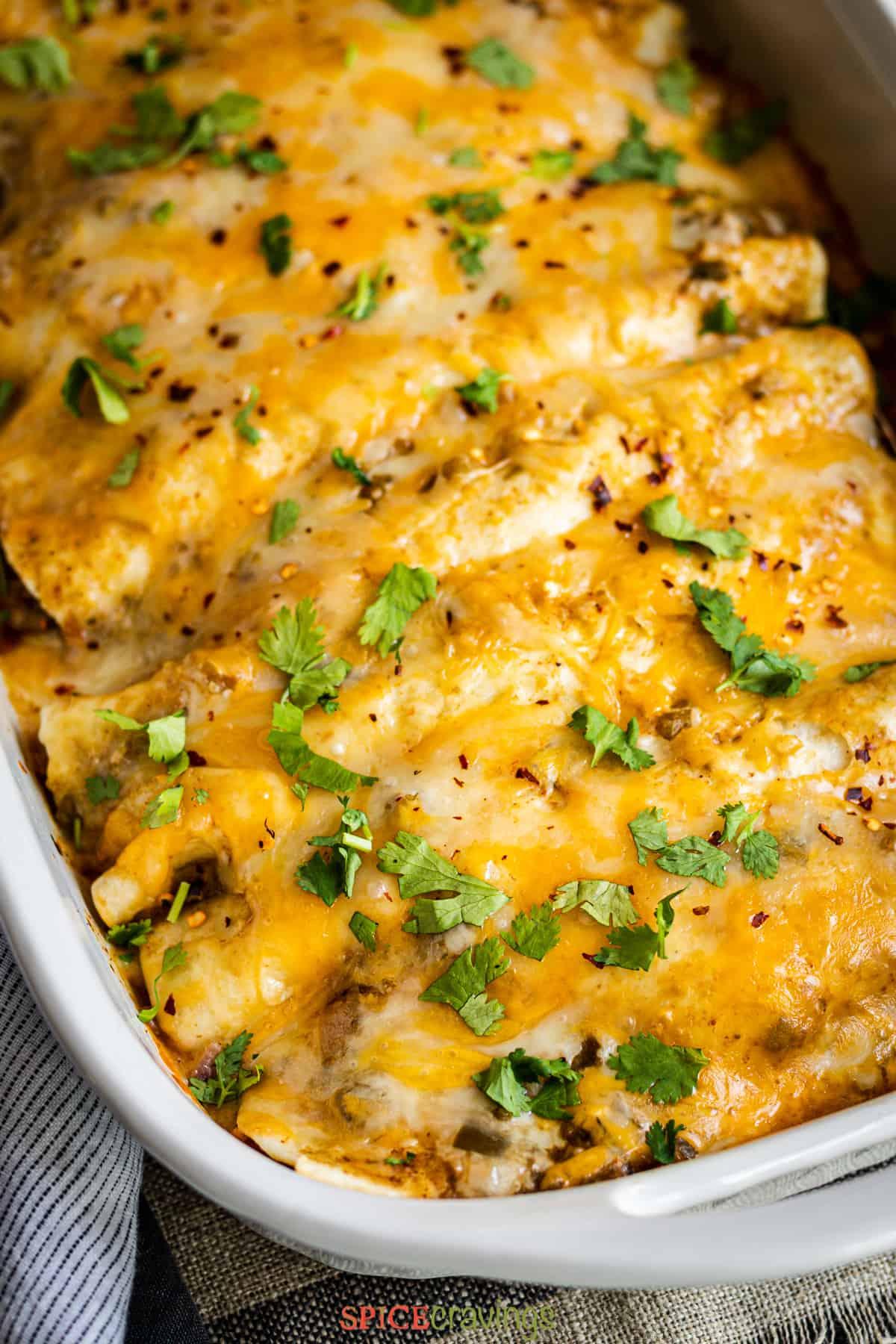 green chile chicken enchiladas in white casserole dish