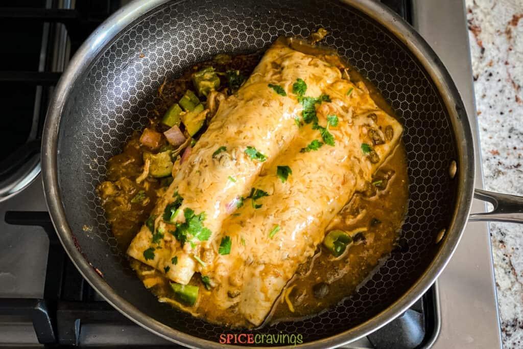 two green chicken enchiladas in hot skillet