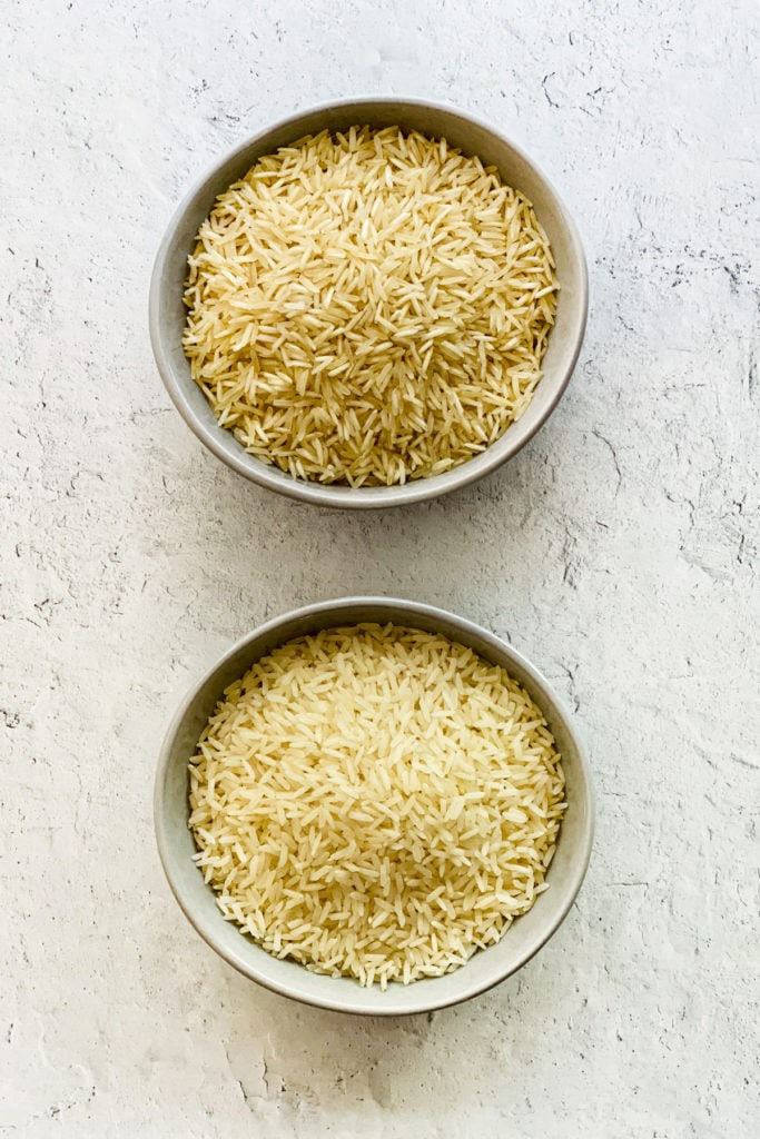 Two grey bowls of uncooked rice, basmati on top, jasmine at bottom.