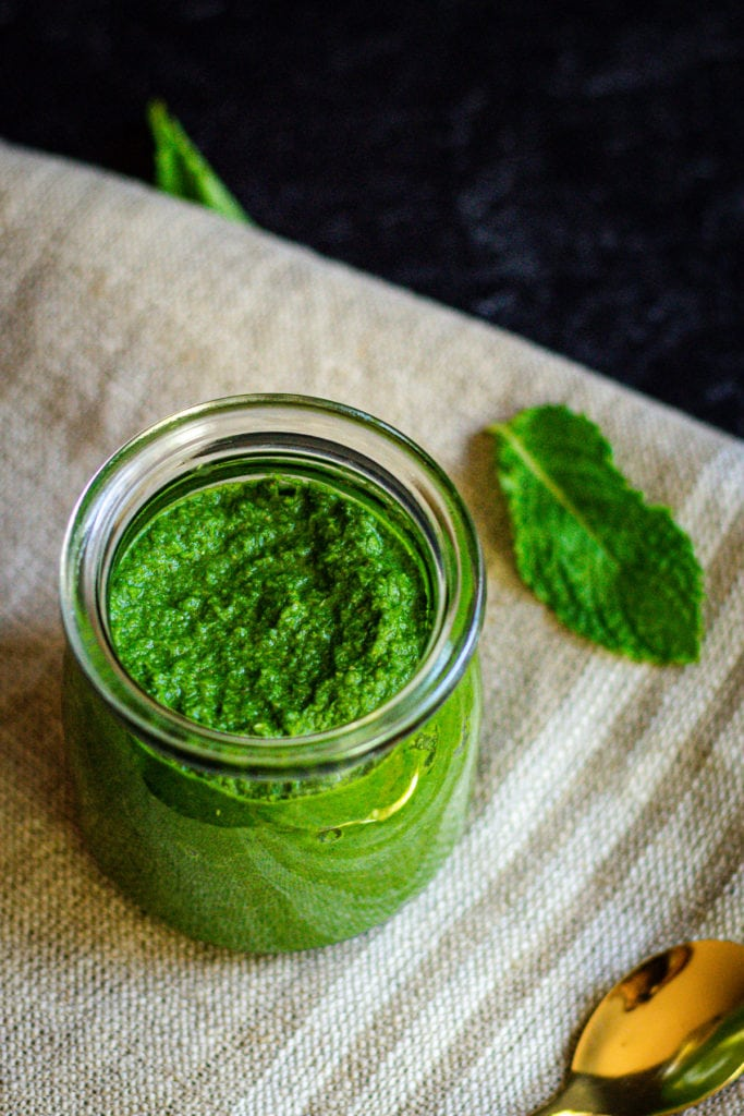 pudina chutney in glass jar with mint leave and gold spoon on the side
