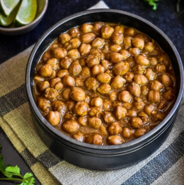 easy punjabi chole recipe in black bowl with lime wedges
