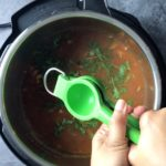 two hands squeezing lime in juicer over tortilla soup in instant pot