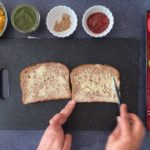 two hands buttering whole grain bread slices with small bowls of condiments on the side