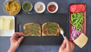 two hands spooning chutney on two whole grain slices with small bowls of condiments on the side