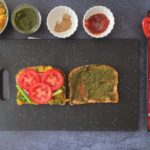 tomato slices on whole grain bread with small bowls of condiments on the side