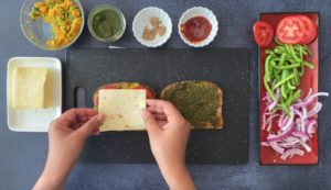 two hands placing slice of cheese on bread with condiments and sliced veggies on the side