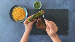 hand spooning cilantro chutney on sliced grilled vegetable sandwich