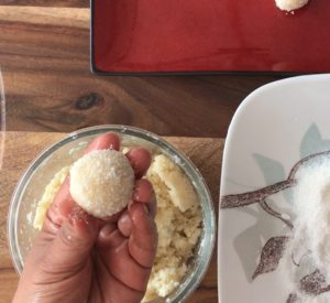hand holding coconut ladoo coated in coconut with dough in glass bowl underneath