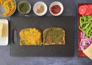two slices whole grain bread layered with ketchup, chutney and potato filling with condiments on the side