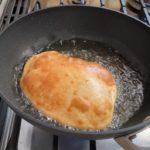 golden brown bhatura bread frying in hot oil