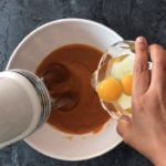 hand pouring eggs into bowl with pumpkin mixture