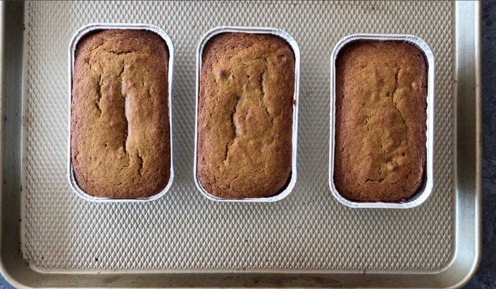 three mini pumpkin loaves in baking pans