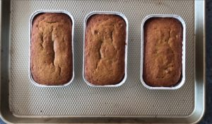 three mini pumpkin loaves in baking pans