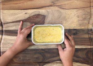 pumpkin cornbread batter in disposable mini loaf pan