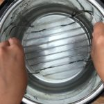 two hands placing trivet in instant pot with water