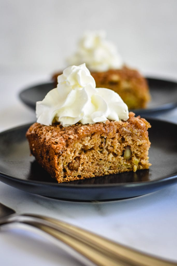 two slices of easy apple cake topped with whipped cream on black plates
