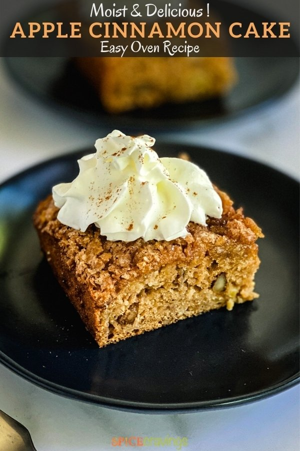square of apple cinnamon cake on black plate topped with whipped cream