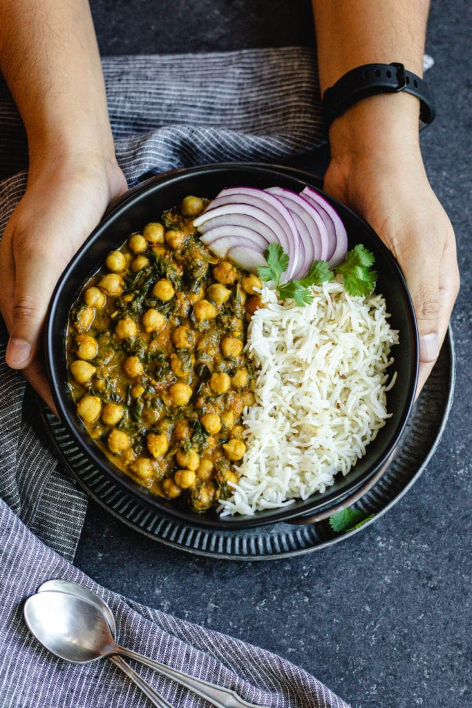 two hands holding chana saag and cumin rice with sliced red onions in black bowl