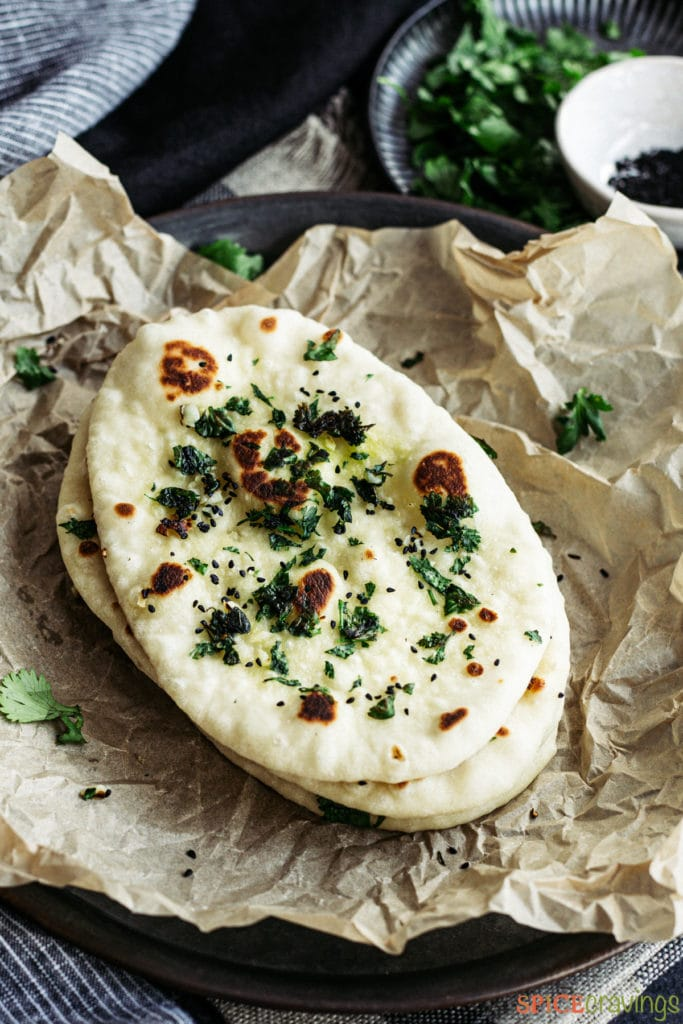 stack of garlic naan on parchment paper