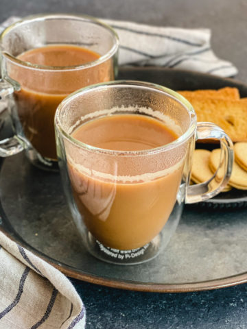 Two cups of Indian tea served with cookies
