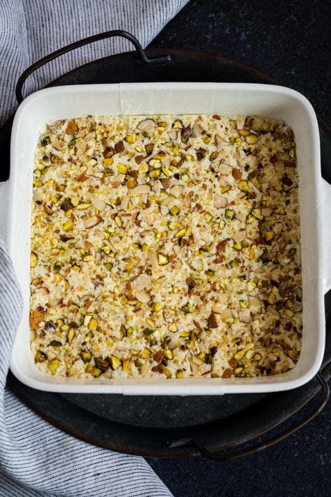 kalakand recipe topped with nuts in baking dish