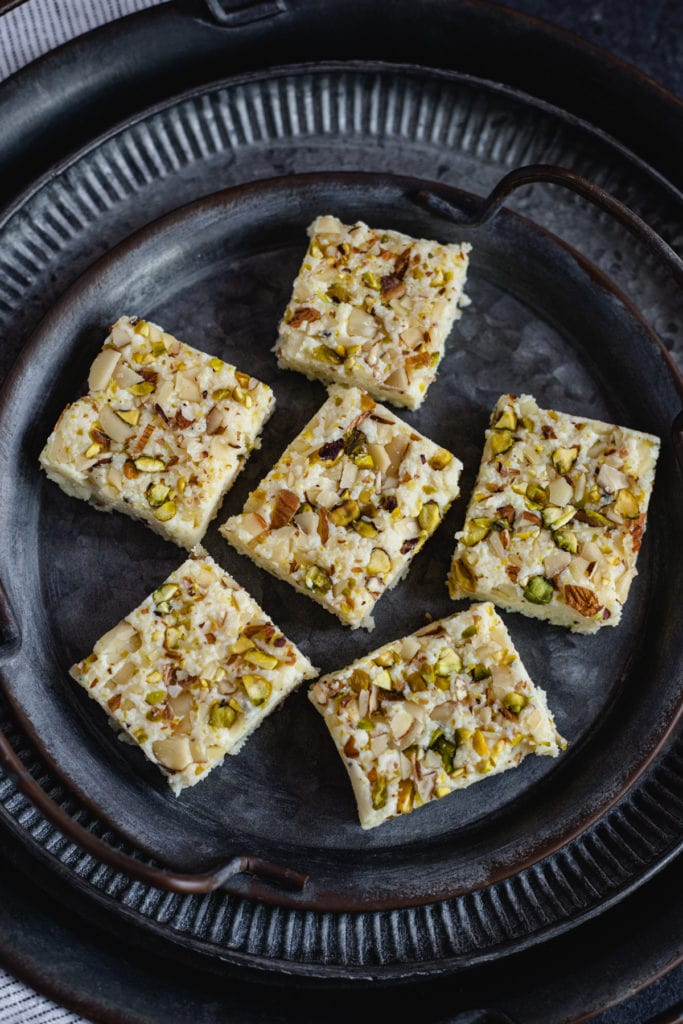 kalakand squares topped with pistachios and almonds on black plate