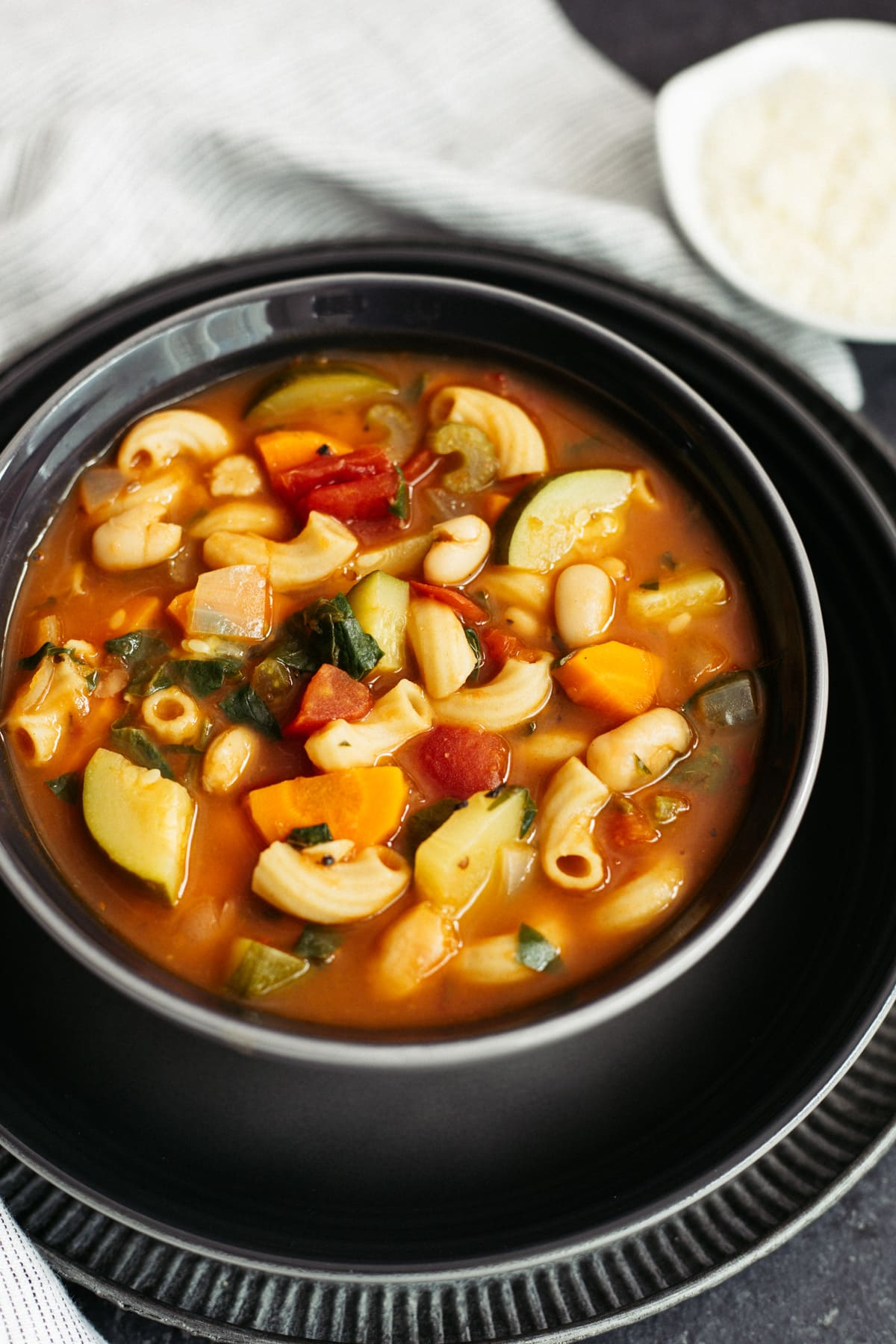 minestrone soup with pasta and vegetables in black bowl