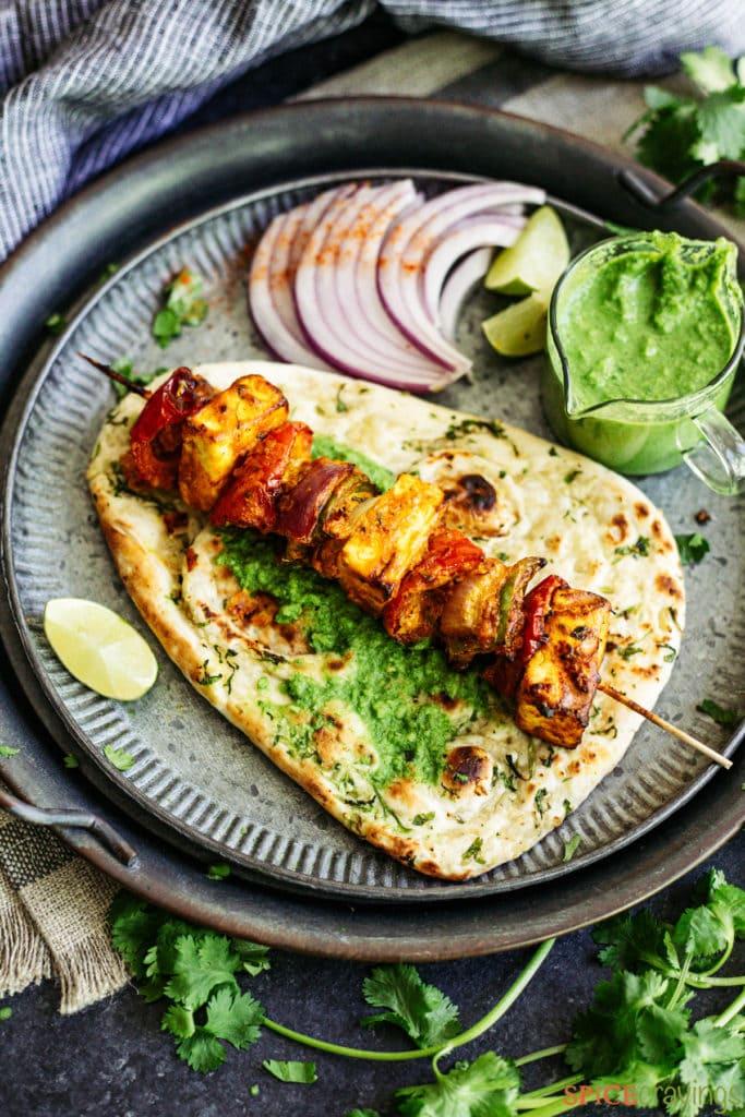 paneer tikka kebab on flatbread with chutney and sliced red onions