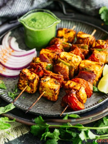 three skewers of paneer tikka on black plate with chutney and onions on side