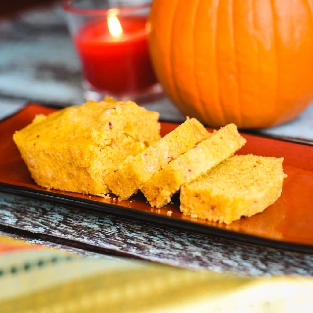 sliced pumpkin cornbread loaf on platter with pumpkin in background