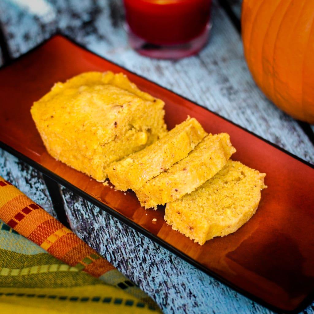 sliced pumpkin cornbread loaf on platter